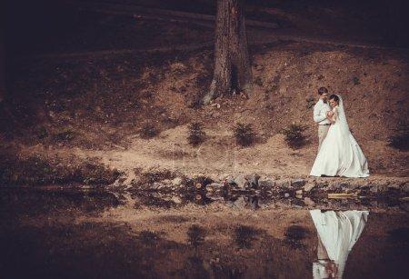 Photo pour Lune de miel. La mariée et marié étreignant sur la rive du lac . - image libre de droit