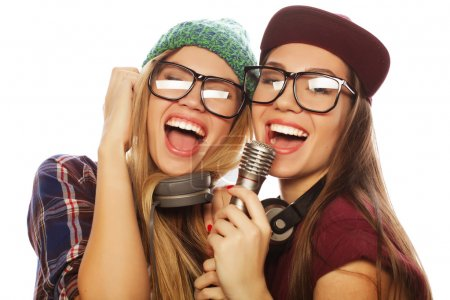 two beauty hipster girls with a microphone singing and having f