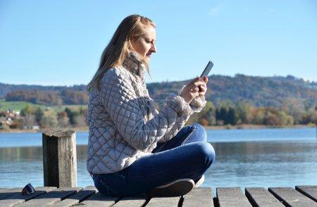 Photo pour Fille lisant à partir d'une tablette sur la jetée en bois contre un lac. Suisse - image libre de droit