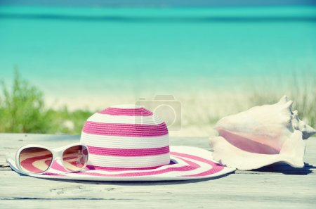 Photo for Sun glasses and hat against tropical beach of Great Exuma island, Bahamas - Royalty Free Image
