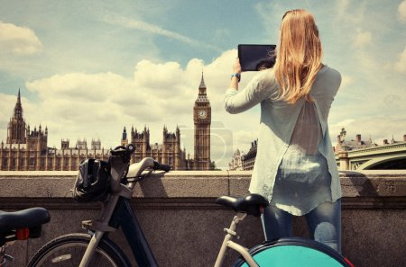 Photo for Girl with a tablet against UK Parliament - Royalty Free Image