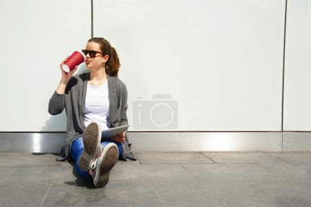 Young teenager drinking coffe and looking aside with tablet