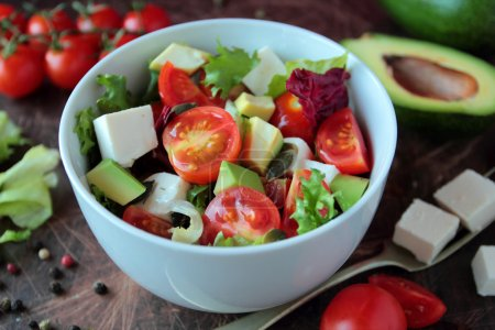 Photo for Fresh vegetable salad with tomatoes avocado lettuce and feta cheese - Royalty Free Image