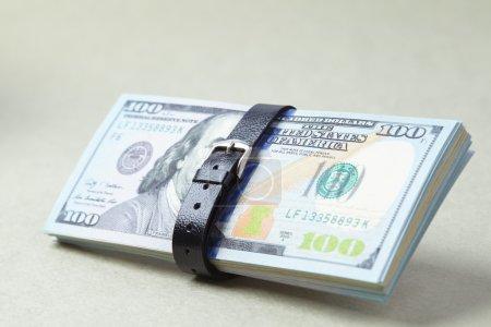 Photo pour Gros plan dollars ceinturés avec ceinture noire - image libre de droit