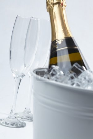 Photo for Closeup champagne glasses and bucket with bottle of champagne in ice on white background - Royalty Free Image