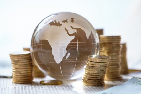 Stacked coins and glass globe, business concept...