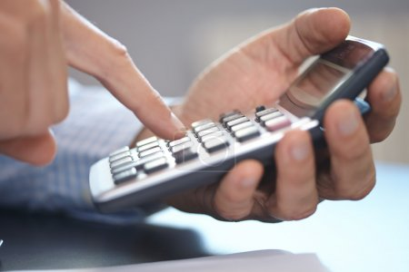 Photo for Businessman with calculator at working place - Royalty Free Image