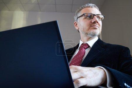 Photo pour Homme d'affaires avec ordinateur portable au bureau - image libre de droit