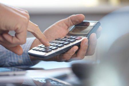 Photo pour Homme d'affaires travaillant avec la calculatrice - image libre de droit