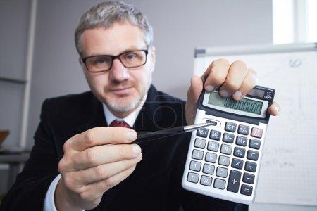 Photo pour Portrait d'homme d'affaires avec calculatrice - image libre de droit
