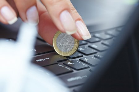 coin on laptop in hand
