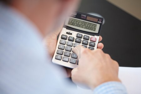 Photo for Businessman using calculator at office - Royalty Free Image