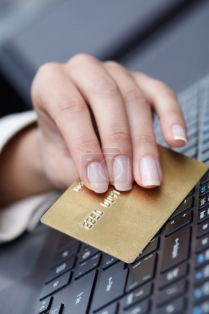 Woman holding credit card on laptop