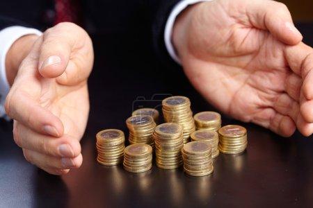 Photo pour Homme d'affaires avec des piles de pièces de monnaie au bureau noir - image libre de droit