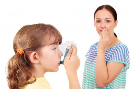 little girl using inhaler due to smoke
