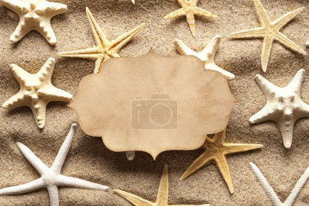 Blank paper card and starfishes on summer beach