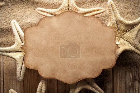 Paper label and starfish on wooden planks and sand