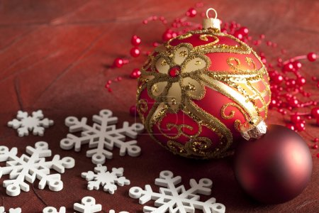 Christmas baubles and snowflakes on red background