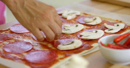 woman making delicious pepperoni pizza