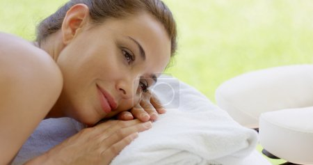 woman resting on folded towel