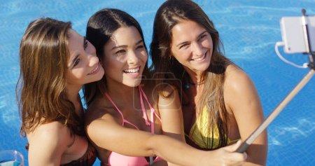Young women taking selfie in pool