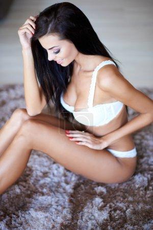 Woman Wearing Lingerie Sitting on Rug on Floor