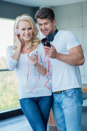 Attractive couple listening to music on headphones