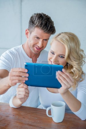 Couple smiling as they read a tablet computer