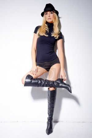 Fashionable sexy woman in boots and a hat