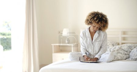 woman writing diary while lying in bed