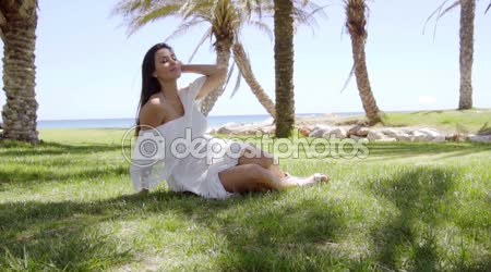 Woman sitting on grass and daydreaming