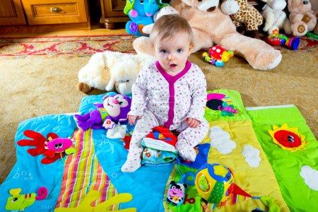 Photo pour Bébé sur le tapis avec des jouets - image libre de droit