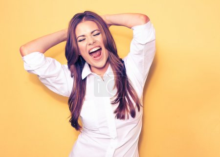 Photo pour Happy emotional business woman portrait. smiling model, white shirt. yellow background. - image libre de droit
