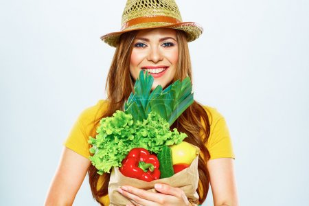 Photo for Smiling woman holding paper bag with green vegan food - Royalty Free Image