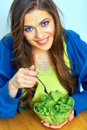 Photo pour Belle fille mangeant de la salade assise à table - image libre de droit