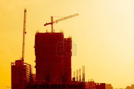 Photo pour Bâtiment industriel au coucher du soleil avec grues sur un immeuble de bureaux ou d'appartements en construction silhouette contre un ciel orange coloré - image libre de droit