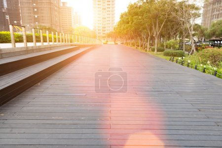 Photo for Deserted walkway and bench steps in an urban park surrounded by high-rise commercial buildings , low angle view - Royalty Free Image