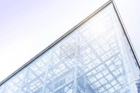 Photo for Low angle view past green foliage of the transparent glass facade of a contemporary urban skyscraper in an architectural background - Royalty Free Image