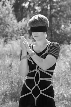 Bound woman with his hands tied and blindfolded. Shibari.