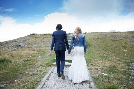 Photo pour Couple marié faisant une promenade sur un chemin pas à pas. On dirait qu'ils montent les escaliers vers le ciel . - image libre de droit