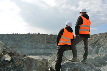 Two workers and quarry in background...