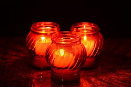 Photo pour Bougies qui brûlent dans un cimetière au cours de la Toussaint. Faible profondeur de champ. - image libre de droit