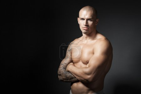 male bodybuilder with folded arms isolated on gray background wi