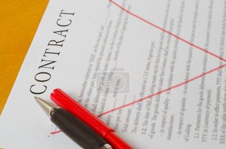 Photo pour Traversé les lignes rouges du contrat avec un stylo couché sur une surface en bois - image libre de droit