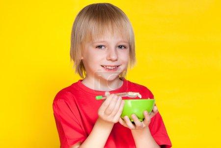 Blond boy eating corn flakes