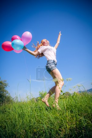 Girl whith balloons in park