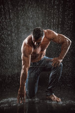 Photo for Very muscular handsome athletic man in the rain - Royalty Free Image