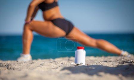 Photo pour Bouteille de nourriture sportive sur le sable contre la fille d'entraînement - image libre de droit