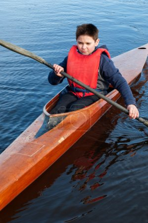 The boy rowing in a kayak on the river