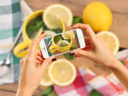 Photo for Woman taking photo of tea with lemon with smartphone - Royalty Free Image